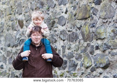 Happy Little Boy Sitting On Father's Shoulders