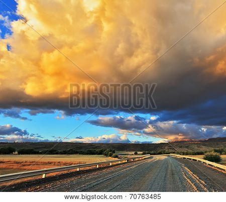 Improbably beautiful huge storm  cloud is shined with the sunset. The cloud hangs over the gravel road