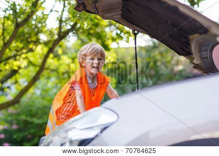 Little Boy Looking At Motor In Family Car