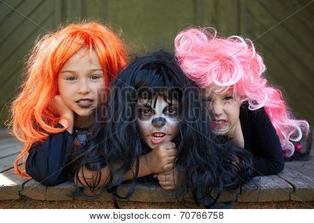 Portrait of three Halloween girls looking at camera with grins