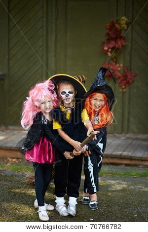 Portrait of three Halloween girls with broom