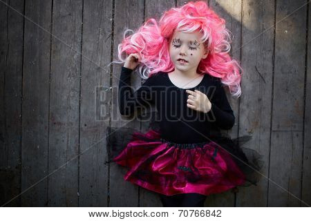 Portrait of cute girl in pink wig having a nap