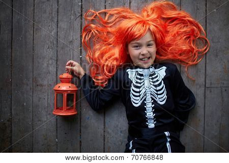 Portrait of cute girl in red wig holding lantern