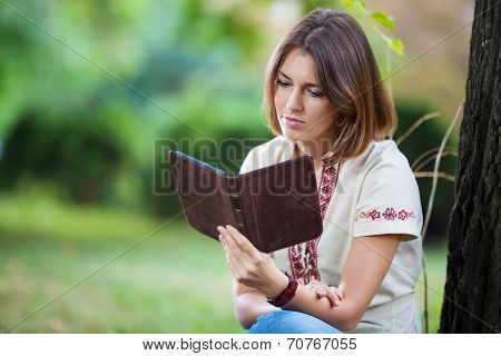 Young attractive woman reading e-book in park