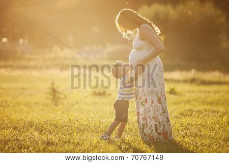 Small boy kissing belly of his pregnant mother