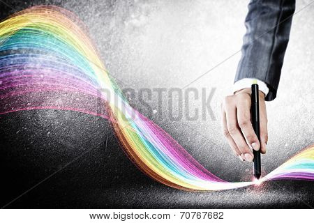 Close up of designer hand drawing colorful loops