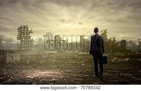 Rear view of businessman looking at ruins of city