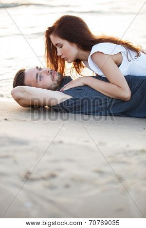 Summer, love. Attractive couple lying on the beach