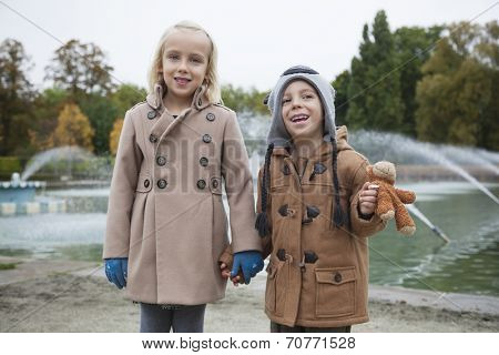 Portrait of happy brother and sister in trench coats holding hands at park