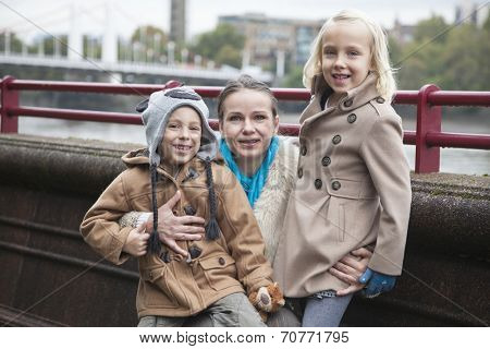 Portrait of young woman with children smiling outdoors
