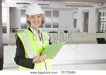 Portrait of smiling senior woman in reflector vest and hard hat holding clipboard at office