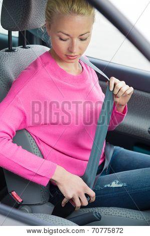 Women driver fastening her seat belt