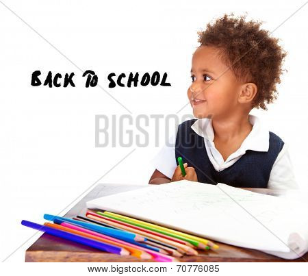 Portrait of cute little African American schoolboy sitting behind the desk and drawing, happy pupil isolated on white background, back to school concept