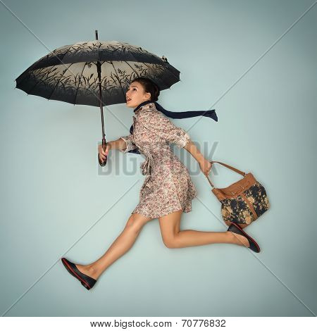 Young woman running hurry up holding umbrella and bag in the autumn rain. Image filtered.