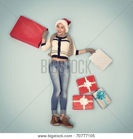 Christmas girl with gift and shopping bags in santa's hat, image toned