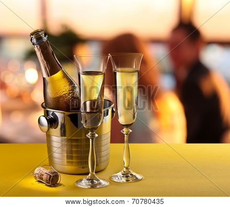 Champagne flutes and chilled bottle at the bar counter.