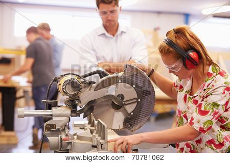 Student And Teacher In Carpentry Class Using Circular Saw