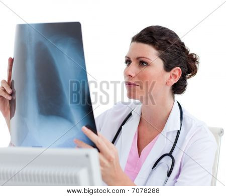 Pensive Female Doctor Looking At X-ray In His Office