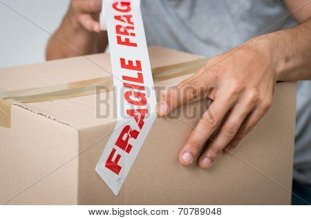 Close up Of A Man Packing Cardboard Box With Sellotape