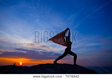 Women Practicing Yoga At Sunset