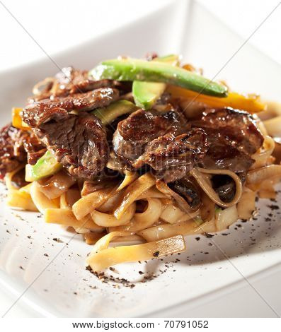 Japanese Cuisine - Udon with Beef and Avocado. Garnished with Cherry Tomato and Avocado