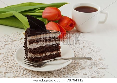 Piece Of Chocolate Layer Cake With Cup Of Tea And Tilips On The Lace Napkin