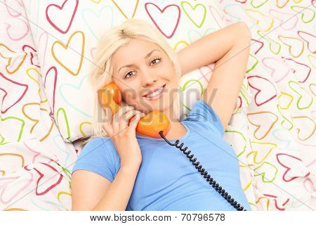 Close-up on a blond woman speaking on the telephone