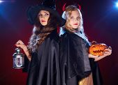 stock photo of warlock  - Two witches with lantern and pumpkin looking at camera in the dark - JPG