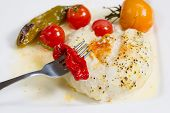 picture of soles  - Closeup of fork and red pepper with baked stuffed sole fish tomatoes green pepper in sauce on white plate - JPG
