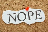 stock photo of slang  - The word Nope typed on a scrap of torn paper and pinned to a cork notice board - JPG