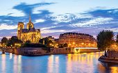 stock photo of notre dame  - Notre Dame Cathedral with Paris cityscape panorama at dusk - JPG