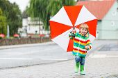 stock photo of rainy season  - Little child having fun with red umbrella wearing colorful raincoat and rain boots outdoors at rainy day - JPG