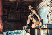 stock photo of cunning  - sexy brutal woman sitting in factory ruins and holding handgun - JPG