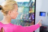picture of dispenser  - Caucasian woman using a vending machine that dispenses snacks - JPG