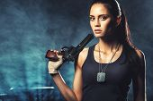 stock photo of handgun  - sexy brutal woman standing on factory ruins and holding handgun - JPG