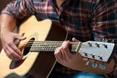 pic of acoustic guitar  - close up of a male musician playing acoustic guitar - JPG