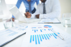 pic of employee  - Documents with chart and graph and pen on background of two employees working - JPG