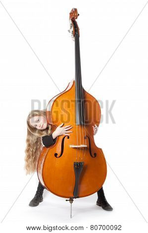 Young Blond Girl Looks From Behind Double Bass In Studio