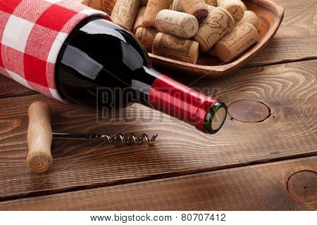 Red wine bottle, bowl with corks and corkscrew. Closeup over rustic wooden table background