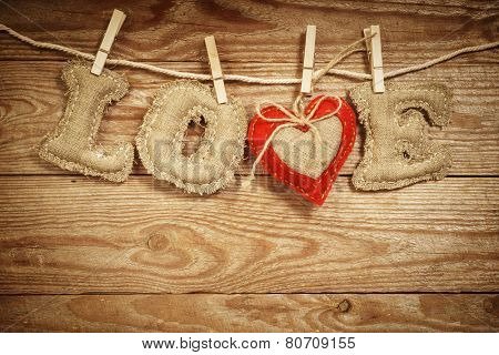 The Love word made of linen letters with a red textile heart on a rope on a vintage wooden background. St. Valentine's day concept.