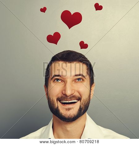 happy laughing man looking up at red hearts above his head over grey background
