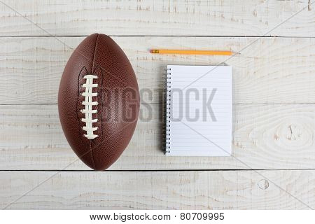 Fantasy Football Draft still life. A pad and pencil and an American style football on a white wood table in a home office.