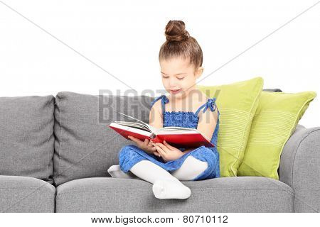 Adorable little girl reading a book on sofa isolated against white background