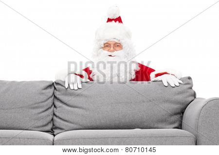 Santa Claus hiding behind a sofa isolated against white background