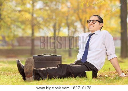Businessman relaxing seated on the grass in park