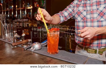 Bartender is decorating cocktail with slice of bell pepper