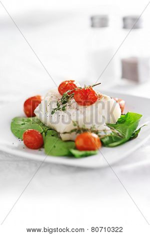 halibut and spinach, cherry tomatoes and thyme on white table cloth