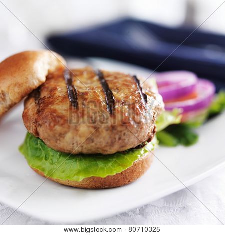 turkey burger on bun with lettuce and fixings close up