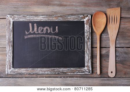 Blackboard menu on rustic wooden planks background