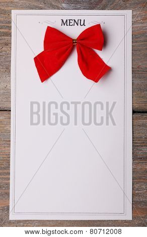 Menu sheet of paper with red bow on rustic wooden surface background